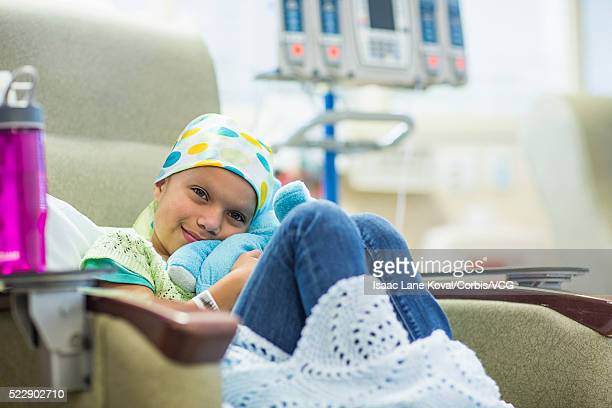 Portrait of young cancer patient (8-9) with stuffed animal