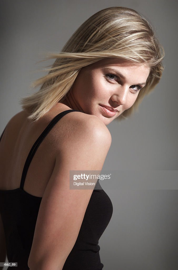 portrait of young caucasian blonde woman in black tank top looks over shoulder flirts with camera : Stock Photo