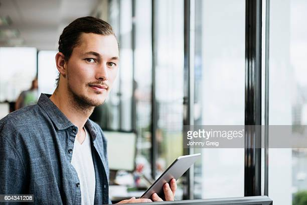 Portrait of young causal businessman with digital tablet