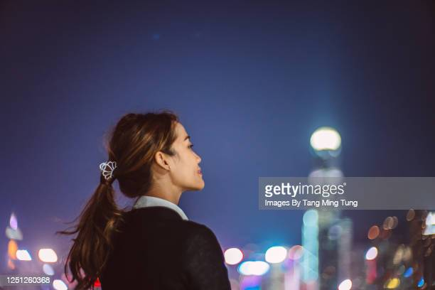 portrait of young cheerful asian woman looking up to sky with confidence against illuminated city buildings - hong kong stock pictures, royalty-free photos & images