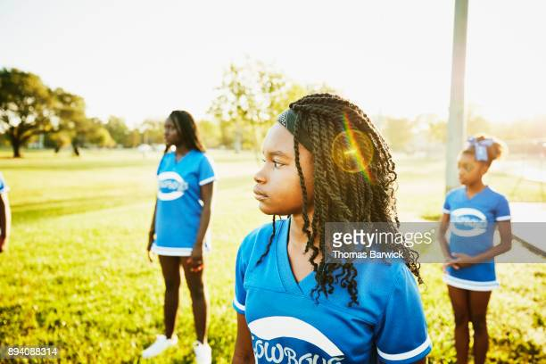 Portrait of young cheerleader during morning practice with teammates
