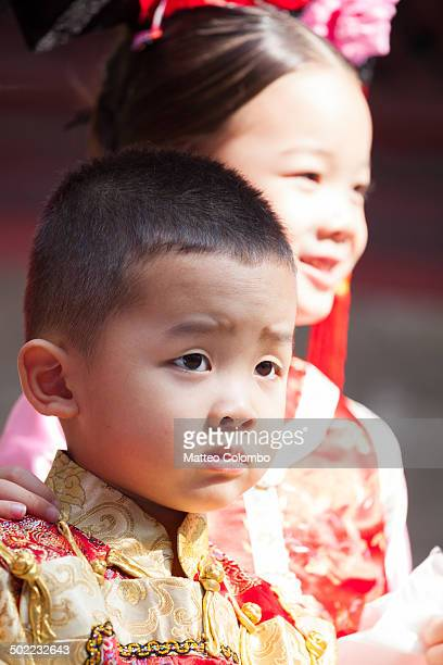 Portrait of young chinese boy with serious expression, behind him a young girl smiling. Both wearing a traditional dress of imperial era.
