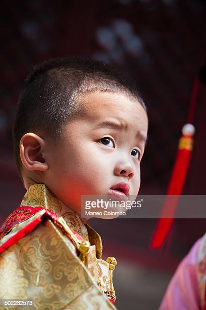 CONTENT] Portrait of young chinese boy with serious expression wearing a traditional dress of imperial era