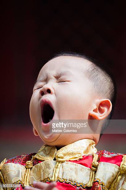 CONTENT] Portrait of young chinese boy yawning wearing a traditional dress of imperial era