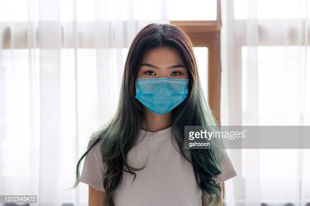 portrait of young chinese woman wearing face mask at home - nurse mask stock pictures, royalty-free photos & images