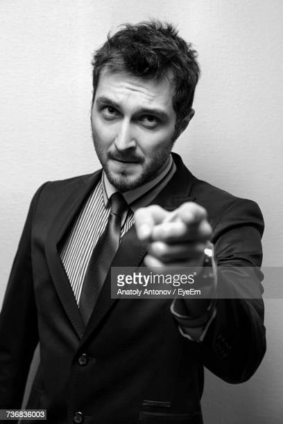 Portrait Of Young Confident Businessman Pointing Against Wall