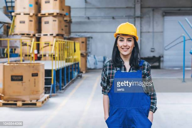 Portrait of young confident female worker in factory warehouse