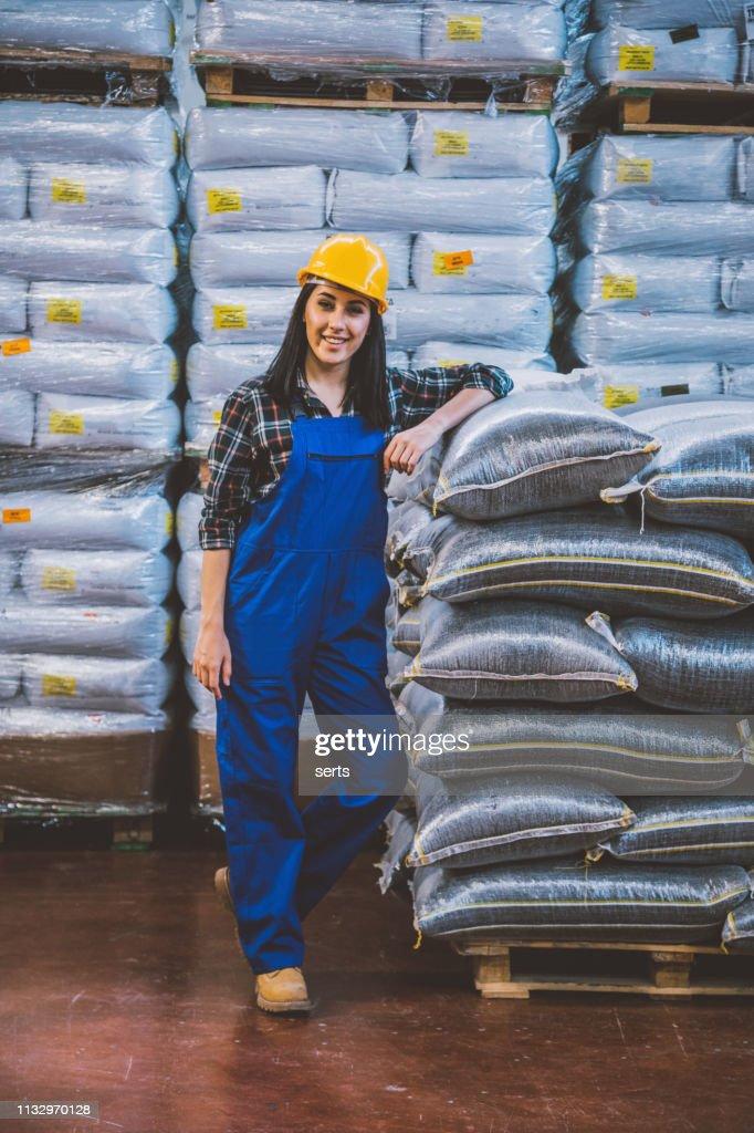 工場倉庫における若い自信の女性労働者の肖像 : ストックフォト