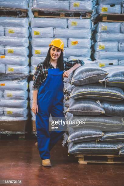 工場倉庫における若い自信の女性労働者の肖像 - カバーオール ストックフォトと画像
