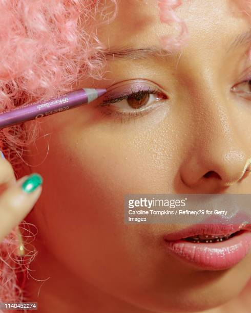 portrait of young confident woman applying eyeliner - eye liner stock pictures, royalty-free photos & images
