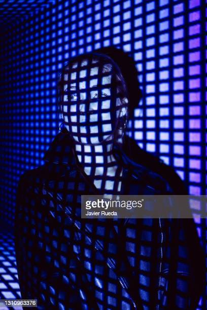 portrait of young confident woman standing against projection screen. she is lighted with squared neon code. - google stock pictures, royalty-free photos & images