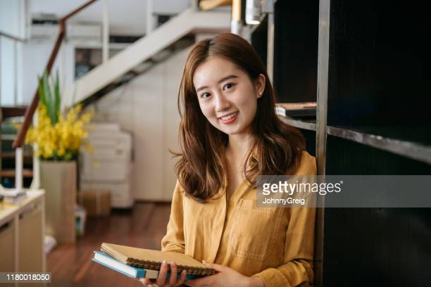 portrait of young contented chinese businesswoman with books - head cocked stock pictures, royalty-free photos & images