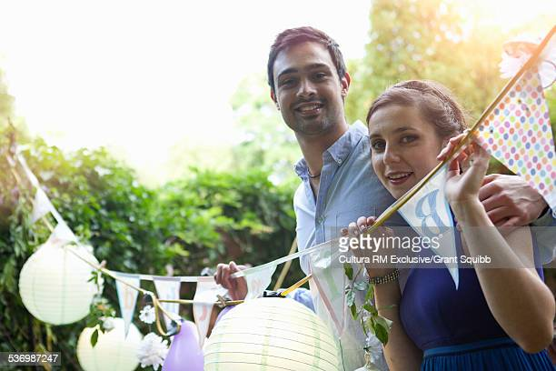 Portrait of young couple and bunting at garden birthday party