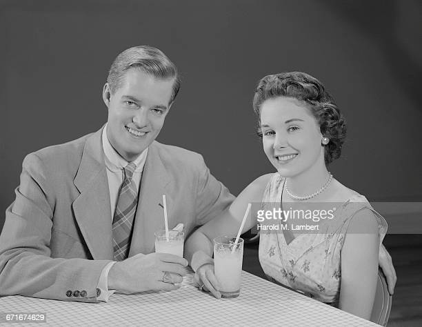 portrait of young couple drinking juice with straw - neckwear stock pictures, royalty-free photos & images