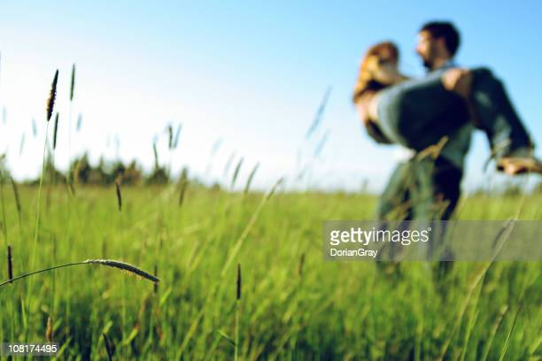Portrait of Young Couple Embracing Outside in Field