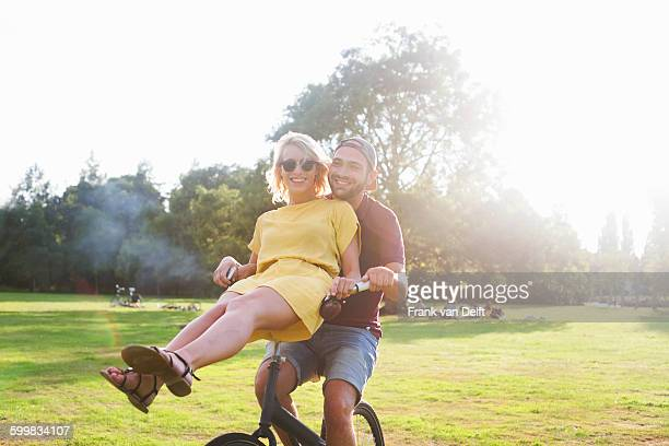 Portrait of young couple having fun on bicycle at sunset party in park