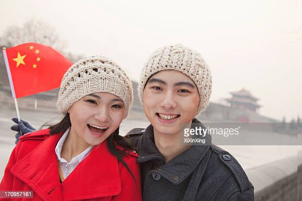 Portrait of young couple holding Chinese flag outdoors in wintertime, Beijing