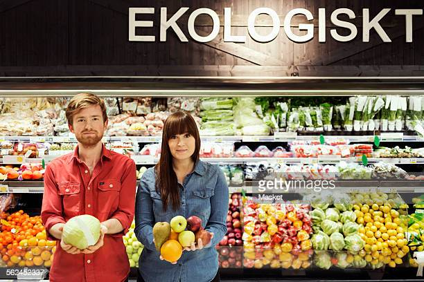 Portrait of young couple holding fresh vegetables in supermarket