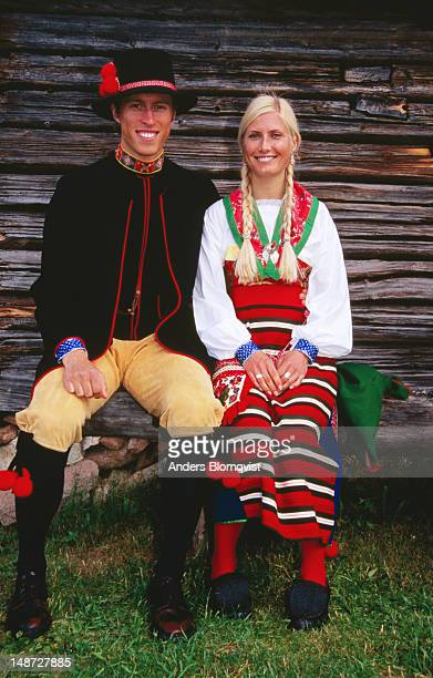 Portrait of young couple in folk costumes sitting by stable.