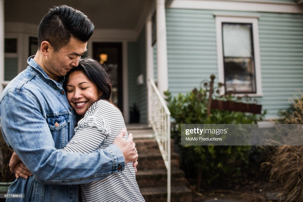 Portrait of young couple in front of home : Stock Photo