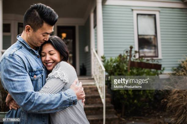portrait of young couple in front of home - home ownership stock pictures, royalty-free photos & images