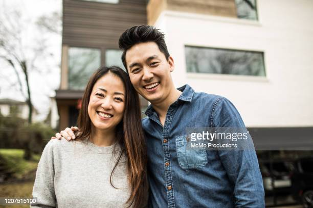 portrait of young couple in front of new home - korean ethnicity stock pictures, royalty-free photos & images