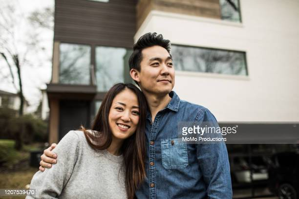portrait of young couple in front of new home - couple photos et images de collection