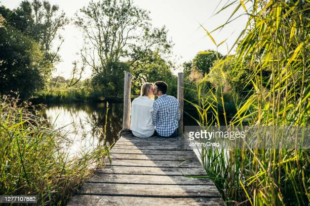 portrait of young couple kissing on dock overlooking pond - west sussex stock pictures, royalty-free photos & images