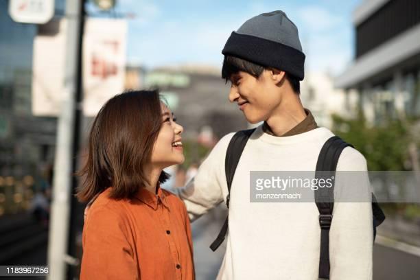 路上でお互いを見つめている若いカップルの肖像画 - 向かい合わせ ストックフォトと画像