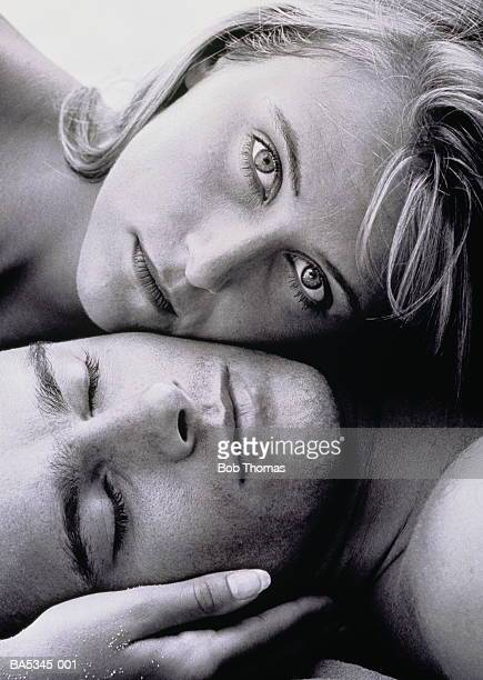 Portrait of young couple lying cheek to cheek,close-up (B&W)