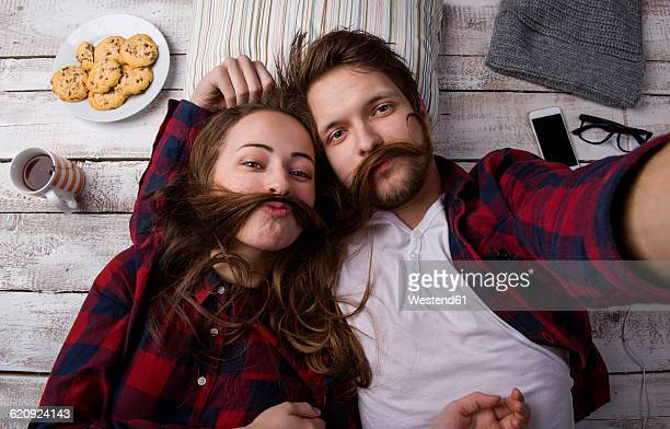 portrait of young couple lying on the floor taking a selfie - hair love stock pictures, royalty-free photos & images