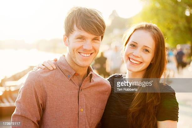 portrait of young couple next to river. - heterosexual couple stock pictures, royalty-free photos & images