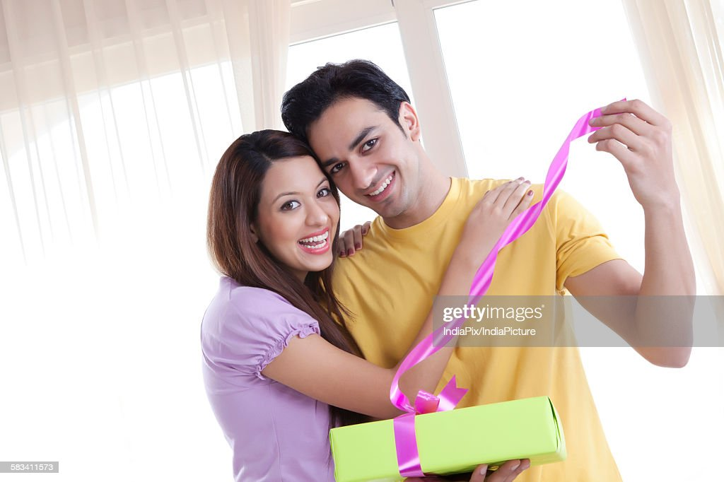 Portrait of young couple opening a gift : Stock Photo
