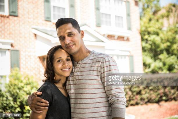 portrait of young couple outside of their home - mid adult couple stock pictures, royalty-free photos & images
