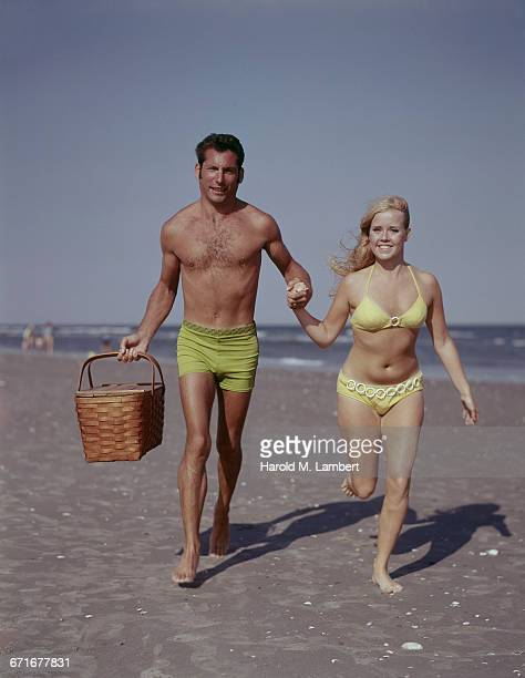 Portrait Of Young Couple Running On Beach