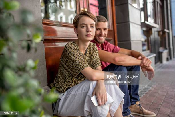 portrait of young couple sitting at the door - heterosexual couple stock pictures, royalty-free photos & images