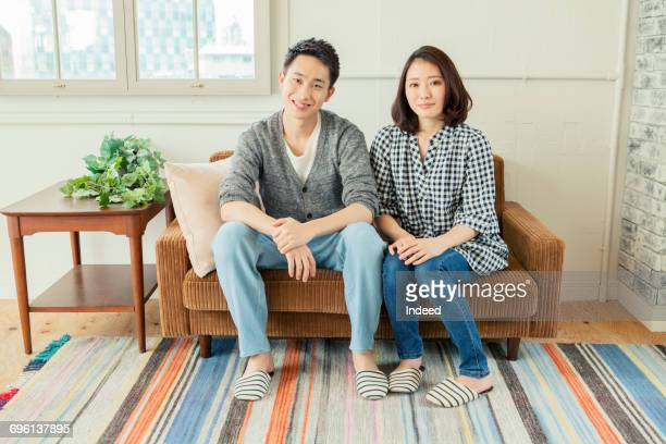 Portrait of young couple sitting on sofa