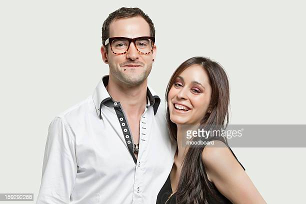 Portrait of young couple smiling together against gray background