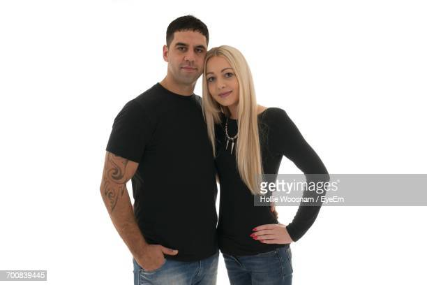 portrait of young couple standing against white background - manches longues photos et images de collection