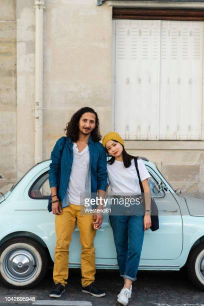 portrait of young couple standing at small car - holding hands in car stockfoto's en -beelden