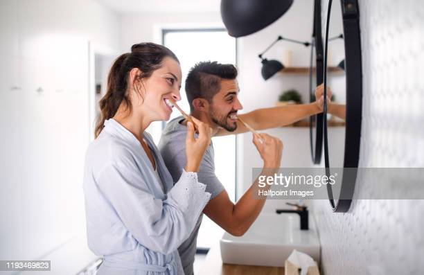 portrait of young couple standing indoors in bathroom at home, brushing teeth. - brushing teeth stock pictures, royalty-free photos & images