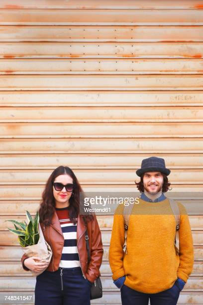 Portrait of young couple standing side by side