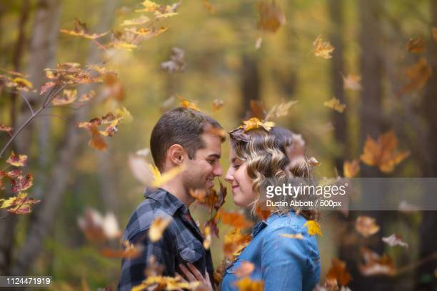 portrait of young couple standing side by side under falling autumn leaves - dustin abbott stock pictures, royalty-free photos & images