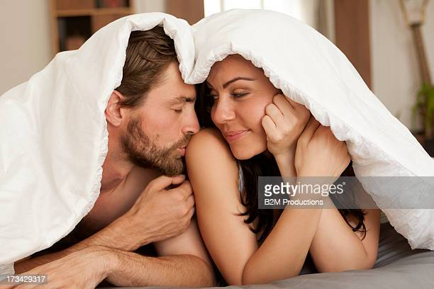 Portrait Of Young Couple Under Bedsheet