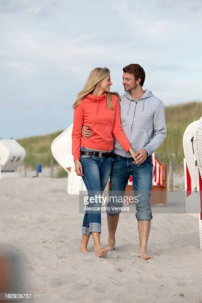 portrait of young couple walking on beach