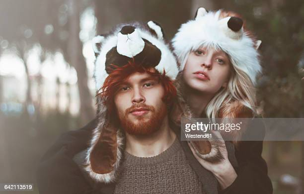 portrait of young couple wearing animal hats in the woods - freaky couples stock photos and pictures