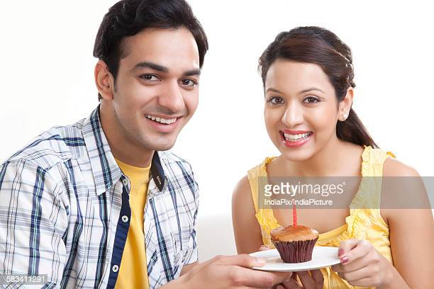 Portrait of young couple with a cupcake