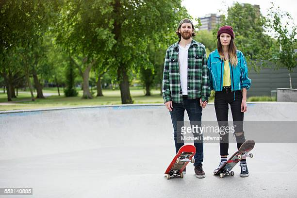 Portrait of young couple with skateboards