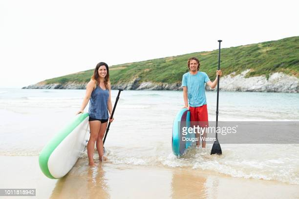 portrait of young couple with stand up paddle boards on beach. - dougal waters stock pictures, royalty-free photos & images