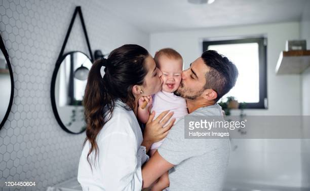 portrait of young couple with toddler girl in the morning indoors in bathroom at home, kissing. - kissing stock pictures, royalty-free photos & images